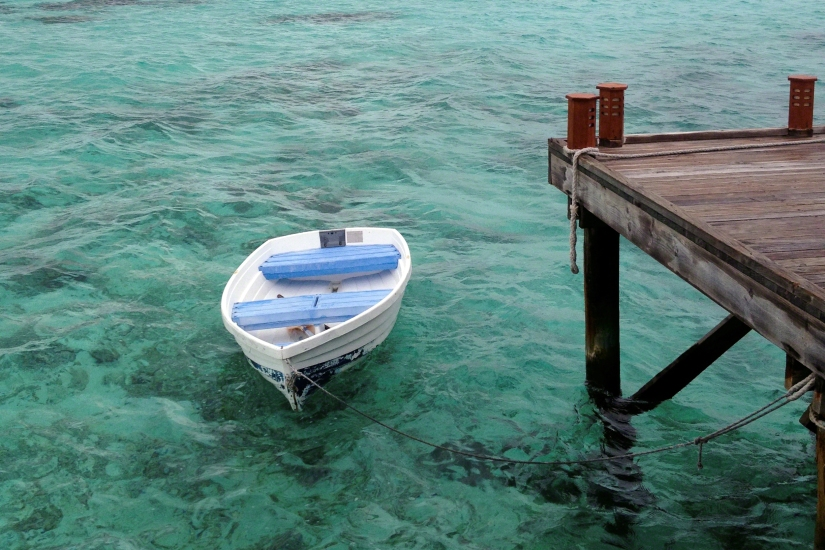A boat drifts in the turquoise water at Mirihi Island Resort, Maldives